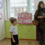 Ребёнок в шапочке игрового персонажа и бабушка-сказочница