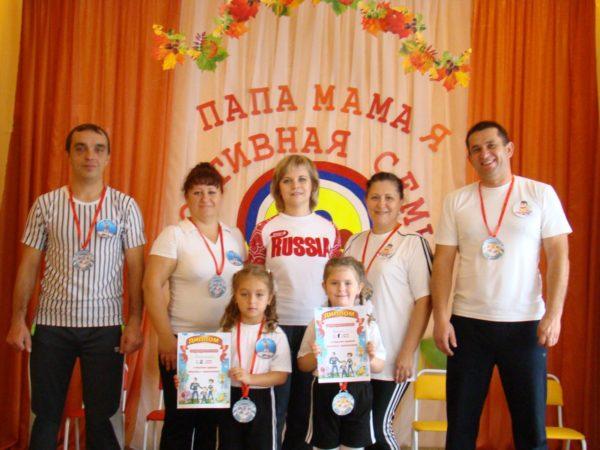Родители и дети стоят с медалями и дипломами