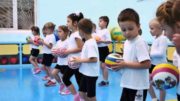 Дети стоят в шеренгу с мячами