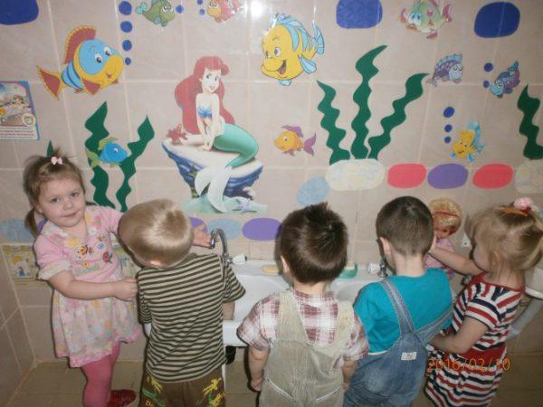 Стена возле умывальников украшена яркими изображениями мультяшных героев