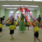 Дети ходят с лентами в руках вокруг педагога в костюме Весны