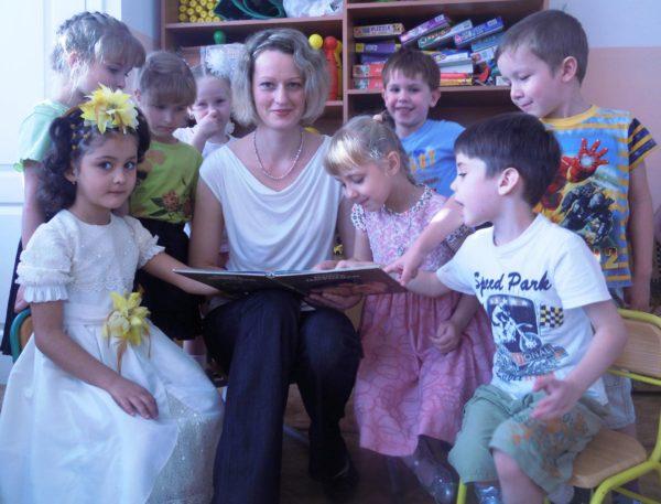 Воспитатель читает книгу детям