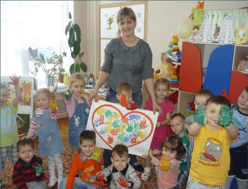 Воспитатель и дети держат картину из сердечек ладошками