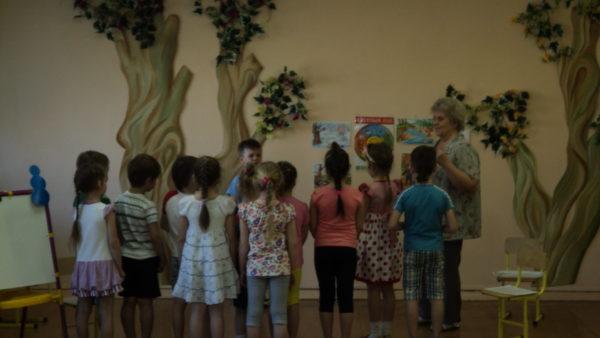 Воспитатель и дети стоят на фоне стены с изображением деревьев