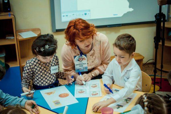 Воспитатель объясняет детям задание по картинкам