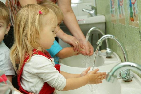 Воспитатель показывает малышам, как мыть руки