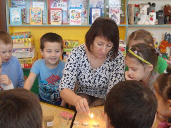 Воспитатель показывает ребятам опыт со свечками