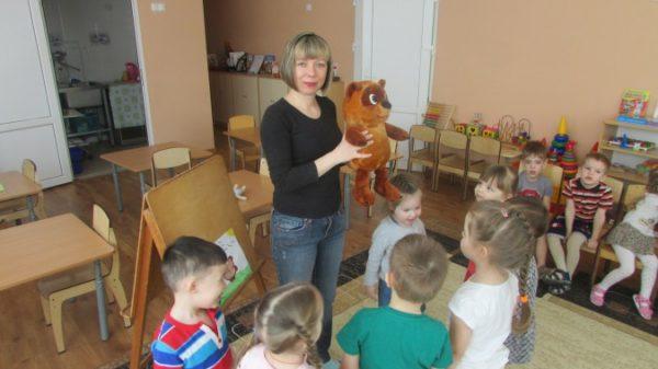Воспитательница держит плюшевого мишку