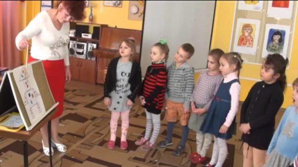Воспитательница показывает указкой на картинку, дети наблюдают