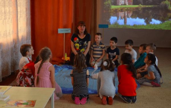 Дети и воспитатель сидят на полу вокруг «Озера доброты»
