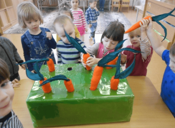 Дети вытаскивают муляжи морковок из зелёной коробки