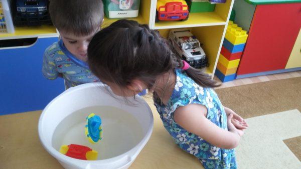 Мальчик и девочка дуют на кораблики в тазике