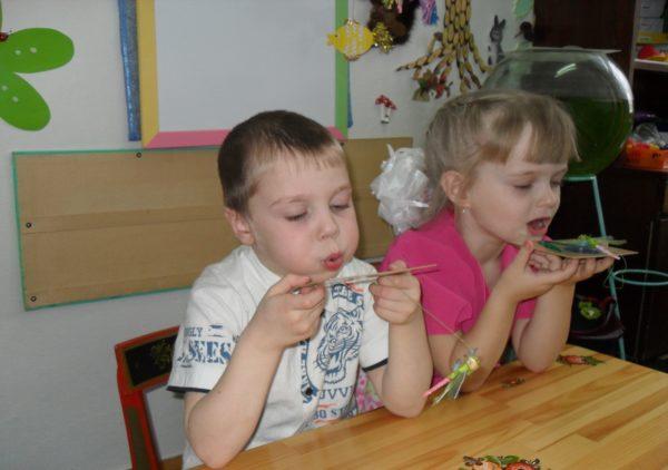 Мальчик и девочка сдувают стрекоз с подставок
