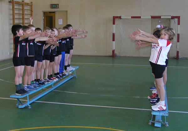 Две команды детей стоят на скамейках в спортзале
