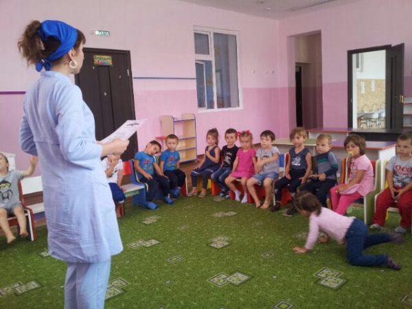 Дети и педагог в белом халате
