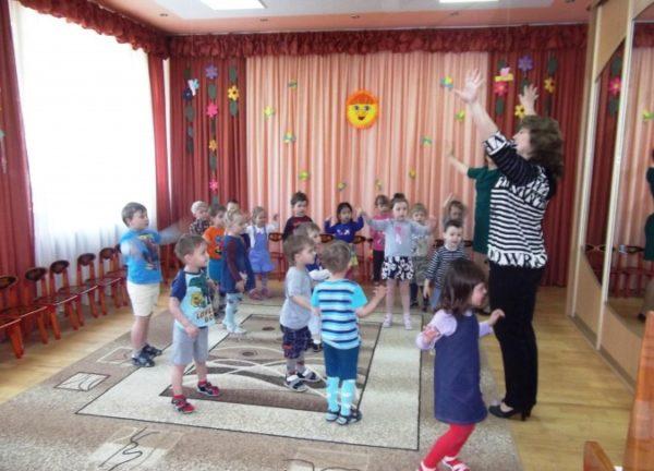 Дети и педагог выполняют упражнение, размахивая руками