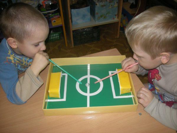 Дети играют в футбол через трубочки для коктейля