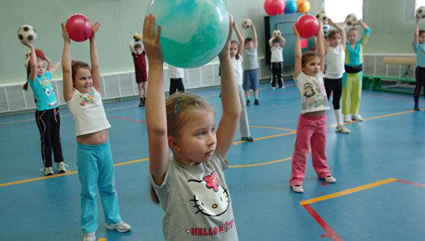 Дети выполняют упражнение с мячами в спортивном зале