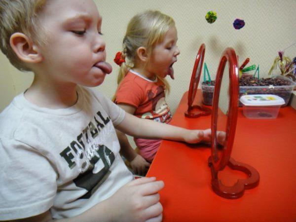 Дети показывают язычки перед зеркалом