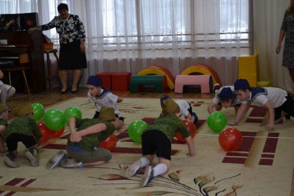 Дети ползут по полу в игре с мячами