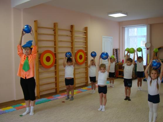 Дети и педагог в костюме Незнайки стоят с поднятыми вверх мячами