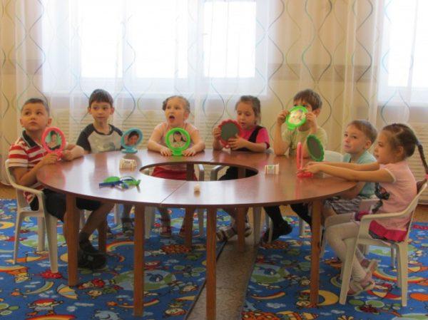 Дети с зеркалами сидят за столом