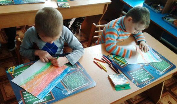 Дети сами закрашивают основу восковыми мелками