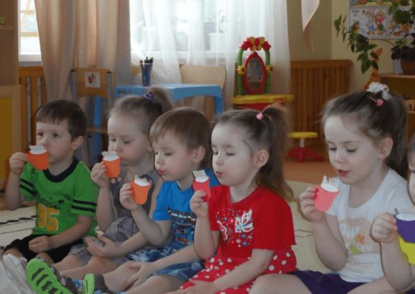 Дети, сидя на ковре, дуют на игрушечные чашечки