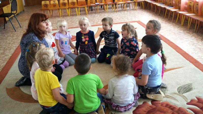 Дети сидят на коврике с педагогом