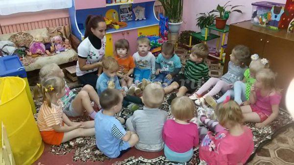 Дети сидят на коврике с воспитательницей