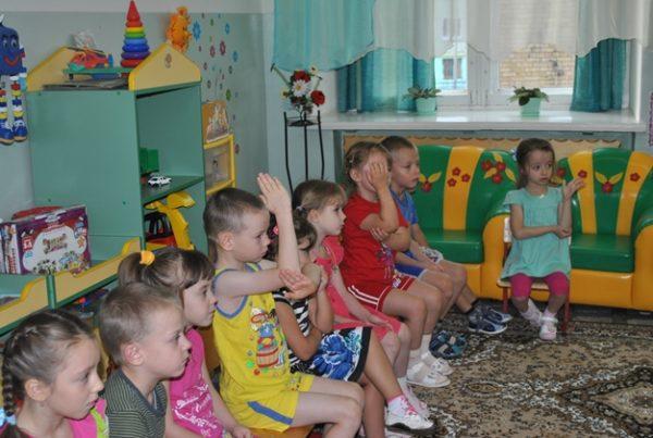 Дети сидят с поднятой рукой для ответа