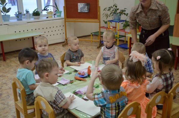 Дети сидят за столом, педагог рассказывает