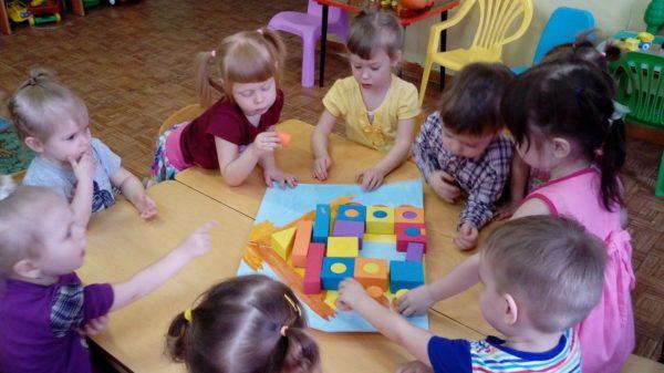 Дети складывают домик из деревянных фигур
