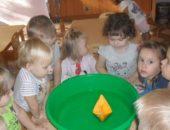 Дети смотрят на бумажный кораблик, плавающий в тазу