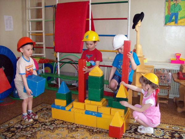Дети строят башню из больших мягких блоков
