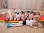 Дети в спортивной форме лежат на полу