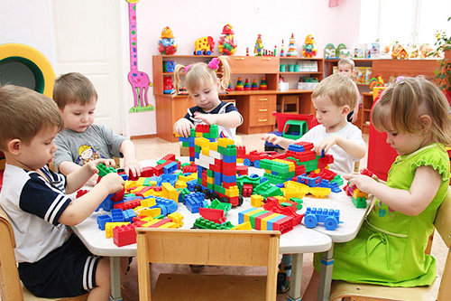 Дети за столом занимаются строительством из деталей конструктора