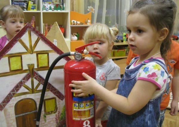 Девочка держит огнетушитель