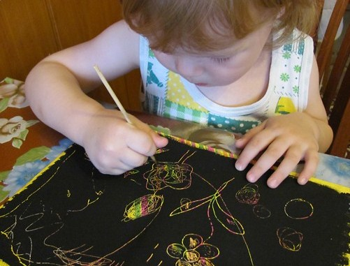 Девочка дошкольного возраста рисует в технике граттаж