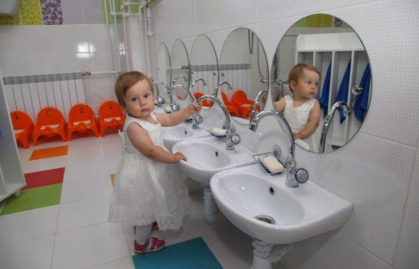 Девочка в белом бальном платье возле рукомойника