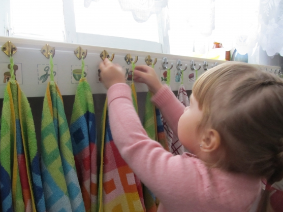 Девочка вешает полотенце на крючок