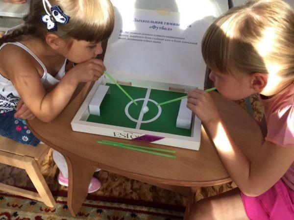 Две девочки играют в воздушный футбол