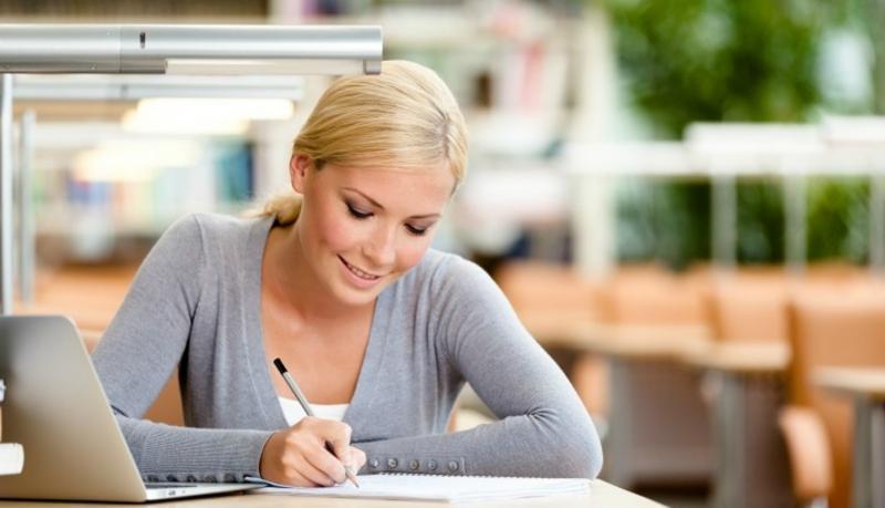 Девушка делает записи в тетради