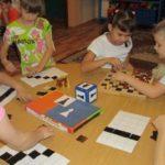 Дети играют с карточками для выкладывания шахматного поля