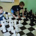 Два мальчика играют в напольные шахматы большого размера