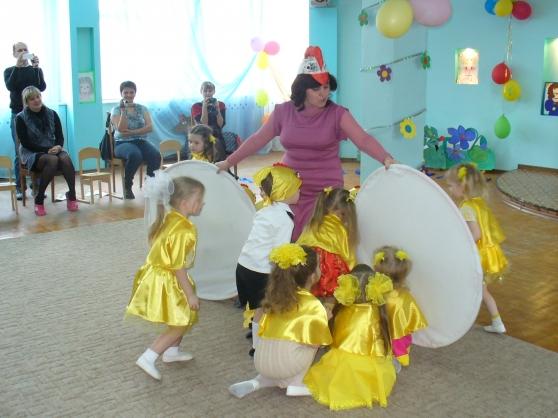 Педагог держит два больших круга перед девочками в жёлтых костюмах