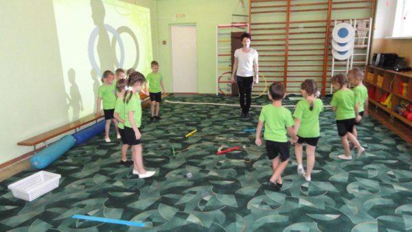 Педагог и дети в зале, на полу разложен спортивный инвентарь
