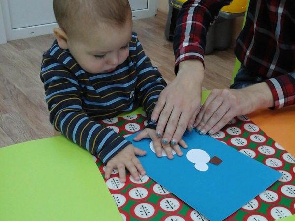 Педагог помогает малышу клеить ватный диск на картон