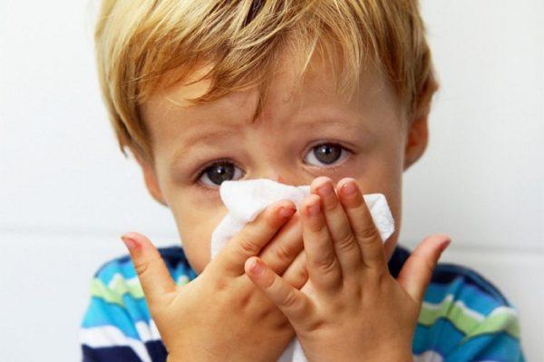 Мальчик держит платок у носа и имеет болезненный вид