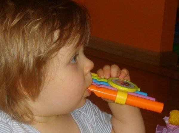 Ребёнок дует в пластиковую свирель